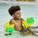 Kind in zwembad met dino zwembandjes
