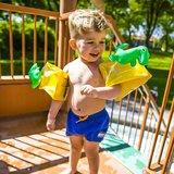 kind blij met dino zwembandjes